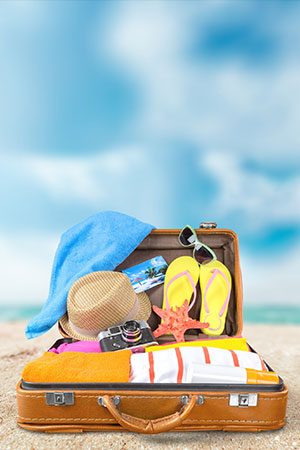 beach and suitcase with hat sunglasses camera towel clothes